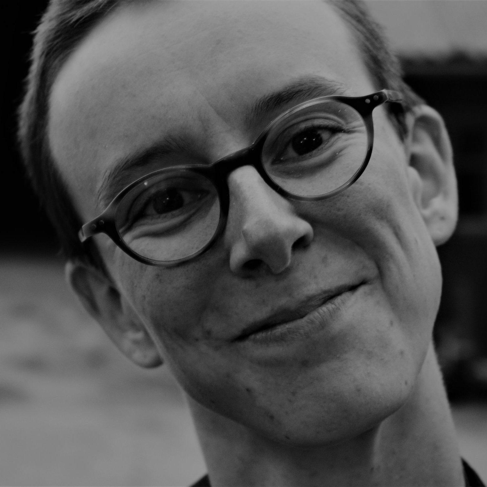 Dieses Bild zeigt eine nicht-binäre, weiße Person mitte zwanzig mit kurzen Haaren und runder Brille in Schwarz-Weiß.